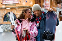 Mixed race couple with snow skis