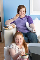 Overweight girl and mother watching television eating