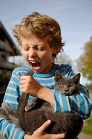 Nine-year-old boy holding cat