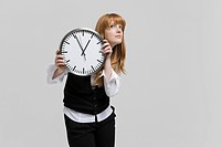 young woman holding wall clock