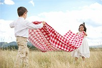 Children Spreading Out Tablecloth