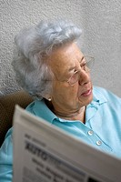 Old woman is reading a newspaper