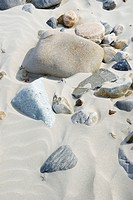 Pebbles of different geological origins polished by wind and sand laying in sand bed