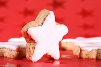 Christmas cookies, cinnamon star cookies on red christmas wrapping paper with stars