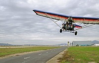 Ultralight aircraft flying in over runway, Camarillo, California, USA