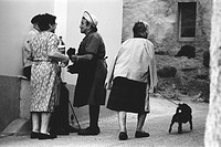 A group of older people chatting on a street Stake Bars, northwest Spain