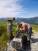 Thirsty hiker drinking from a well, Saukarlalm alpine pasture, Grossarltal, Salzburg, Austria, Europe