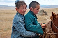 Rosy-faced Mongolian boy and girl on horseback, north central Mongolia No releases available