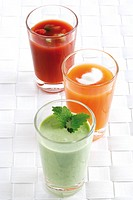 Three kinds of soup served in a glass: gazpacho, carrot soup and pea cream soup garnished with mint