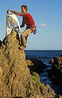 Extreme ironing, ironing a shirt on top of a rock pinnacle Houghton Bay Wellington New Zealand