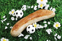 Football fast food - bratwurst and mini footballs on lawn
