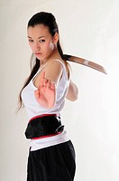 East Asian girl practicing Kung Fu with sword, rage, vengeance