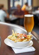Lobster poutine with glass of beer in restaurant Canada