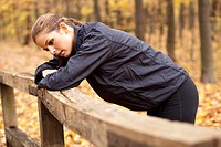 Young female jogger exhausted in autumnal forest