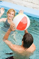 Man and woman playing with beach ball in swimming pool