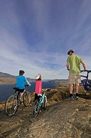 A family on a mountain bike outing take in the stunning view over Kamloops Lake, west of Kamloops, British Columbia, Canada