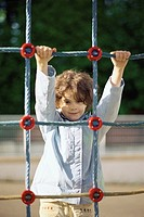 Little girl on rope climbing net, portrait