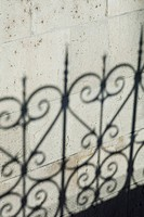 Shadow of ornate fence on wall