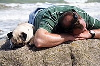 Man with a pug sleeping on a rock in front of the sea