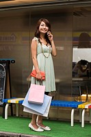 Young woman talking on a mobile phone outside a cafe while shopping, Tokyo, Japan, Asia