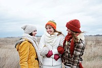 Three laughing teenage girls wearing hats and scarfs