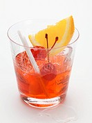 Manhattan with cocktail cherries and orange wedge