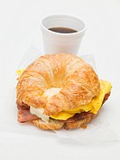Croissant with bacon, scrambled egg & cheese, cup of coffee