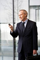 A businessman looking at a mobile phone holding a briefcase