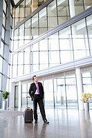 A businessman waiting with suitcase in office or airport building