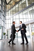 A businessman greeting a client in the foyer of an office building