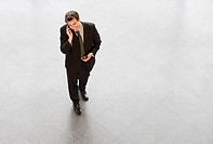 A businessman walking and talking on his mobile phone
