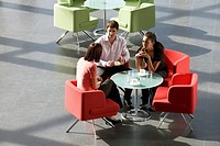Three business colleagues having a meeting over a hot drink in an office building (thumbnail)