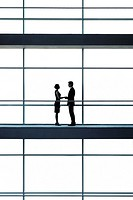 A businessman and woman on a walkway of a large modern office building, shaking hands