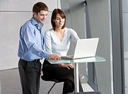 A businessman and woman in office looking at a laptop