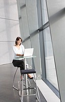 A businesswoman sitting in modern office building using a laptop