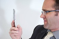 side view of businessman with spectacles checking mobile for text messages