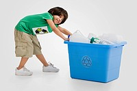 Hispanic boy pulling recycling bin