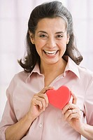 Hispanic woman holding heart_shaped object