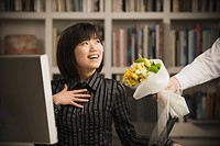 Man giving Asian businesswoman bouquet of flowers