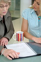 two businesswomen talking about document on table