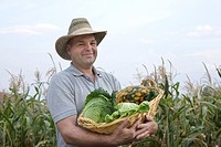 portrait of farmer holding basket with cabbage and pumpkins