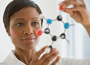 African scientist holding molecule model
