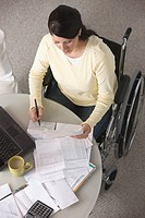 Hispanic woman in wheelchair paying bills