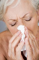 A senior woman blowing her nose