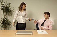 businessman cutting his own tie while female colleague is pulling it