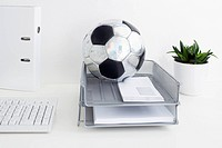 still life of football in tray on office desk