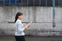 young businesswoman standing in front of factory building holding plan in hands