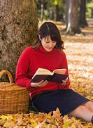 Mixed race woman reading under tree in autumn