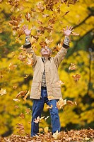 Hispanic man throwing autumn leaves