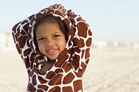 Young mixed race girl wearing hoody at beach